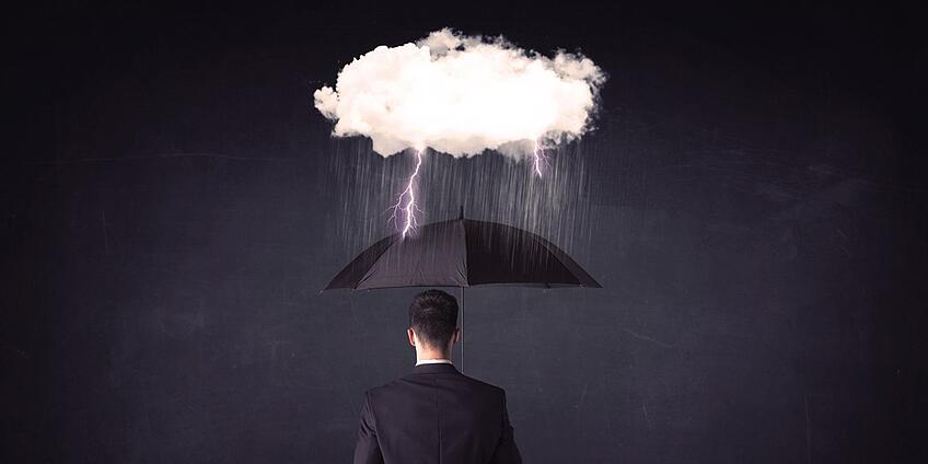 Businessman standing with umbrella and little storm cloud concept on background-2