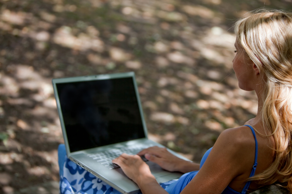 Woman working on a laptop computer outdoors